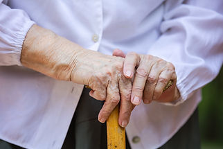A senior woman's hands holding a walking stick or cane.