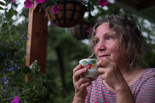 A senior woman enjoying a cup of tea or coffee outside her home.