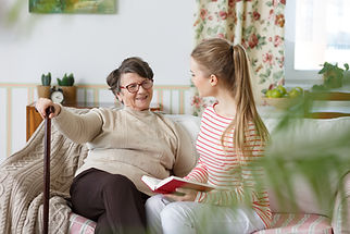 Lady with walking cane sitting on couch beside caregiver and/or younger family member.