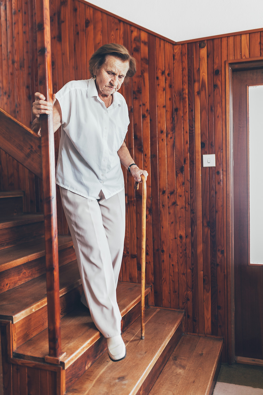 Senior woman using cane and vertical rail to navigate wooden steps.