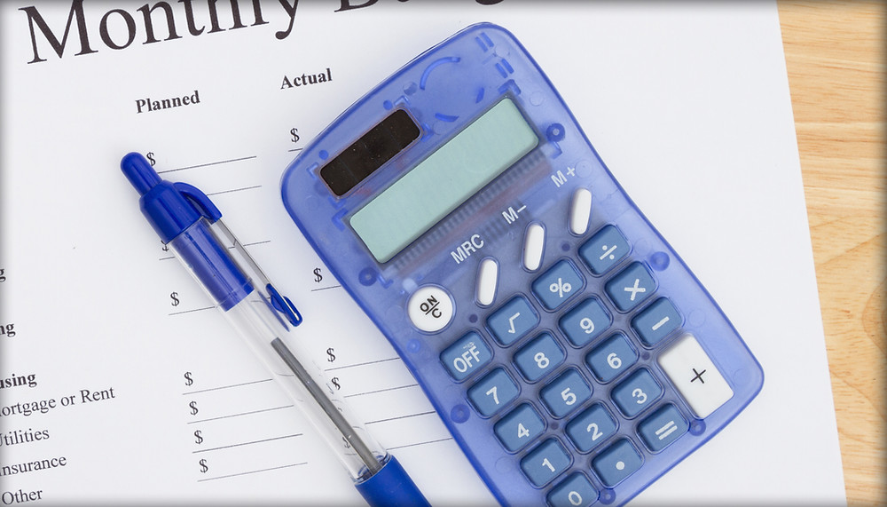 Blue calculator and pen on monthly budget paper