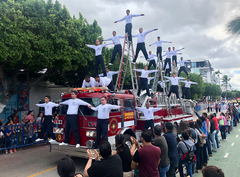 firemen balancing on fire engine