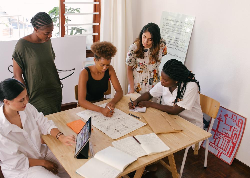 Mulheres diversas reunidas em torno de uma mesa, trabalhando em um projeto