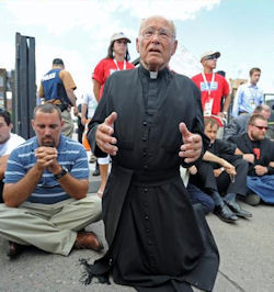Father Weslin Praying in front of clinics.jpg