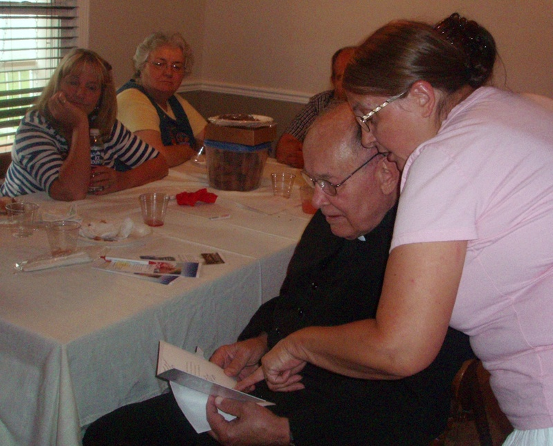 Father Weslin Reading Cards at the unwed mothers home he founded.jpg
