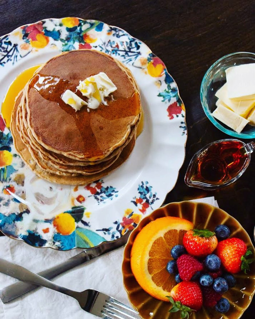 Pancakes on colorful floral plate with butter, maple syrup, and fresh fruit