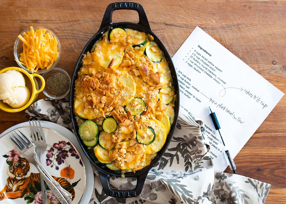 A vegetable casserole in a cast iron pan with a menu in the background, shredded cheese, butter, salt and pepper, and a colorful place setting