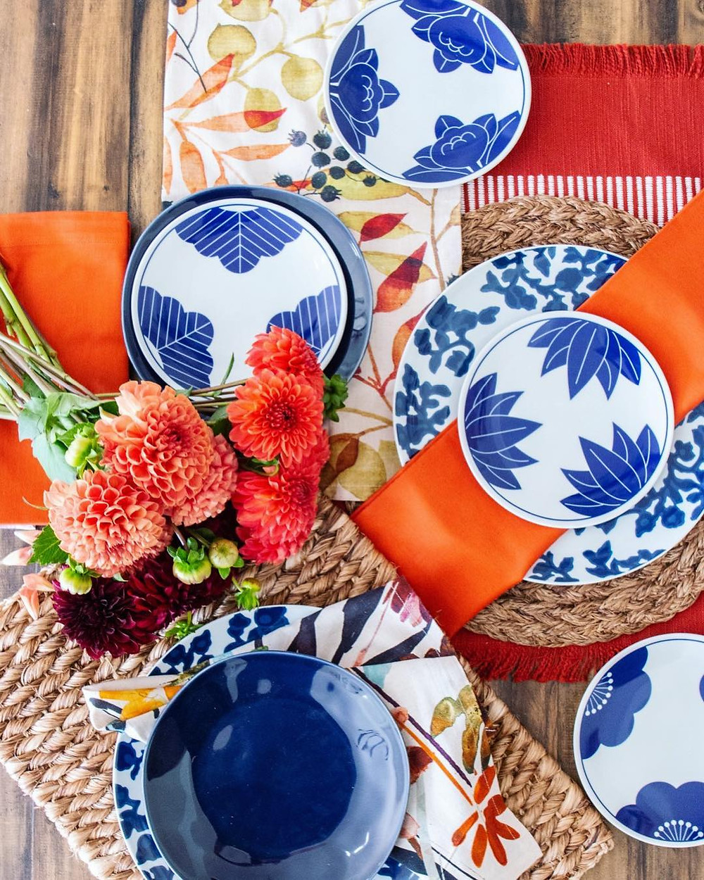 Tablescape with red linens, blue and white china plate settings, colorful napkins, and a floral arrangement