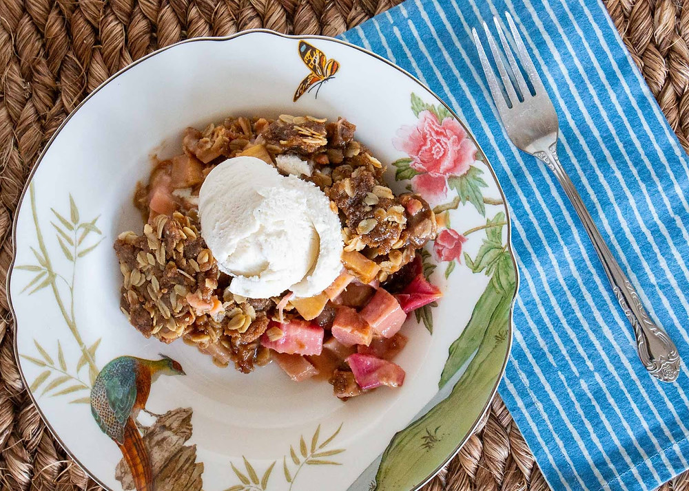 A rhubarb cobbler with oats and vanilla ice cream on a colorful plate