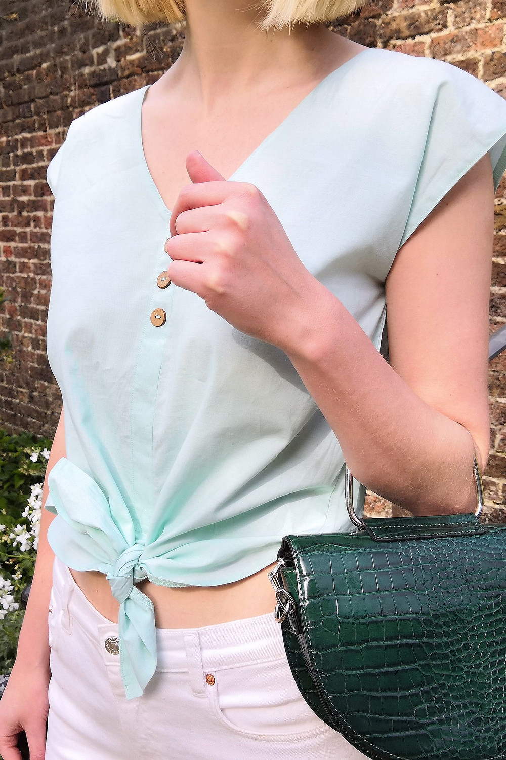 Outfit detail with pastel mint blouse, white denim and mock croc bag