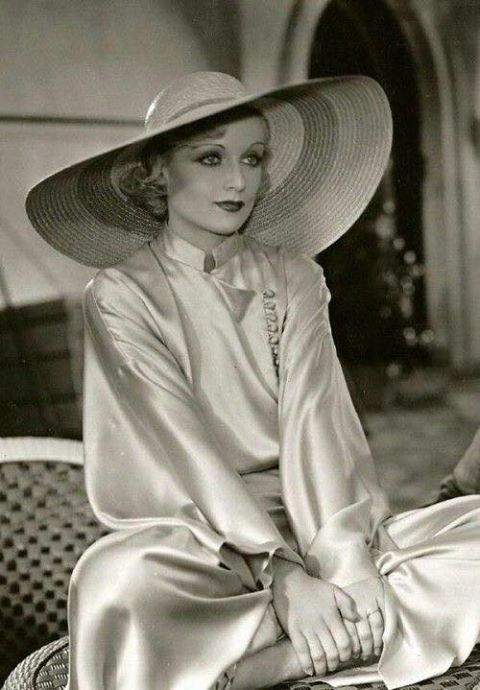 Carole Lombard in a silk gown with wide hat