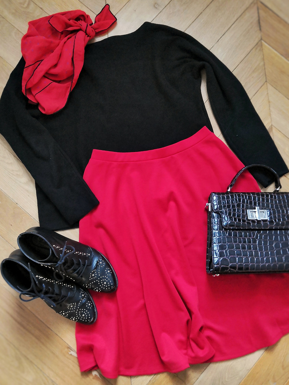 Flatlay outfit with sweater, red skater skirt, neckscarf, handbag and boots