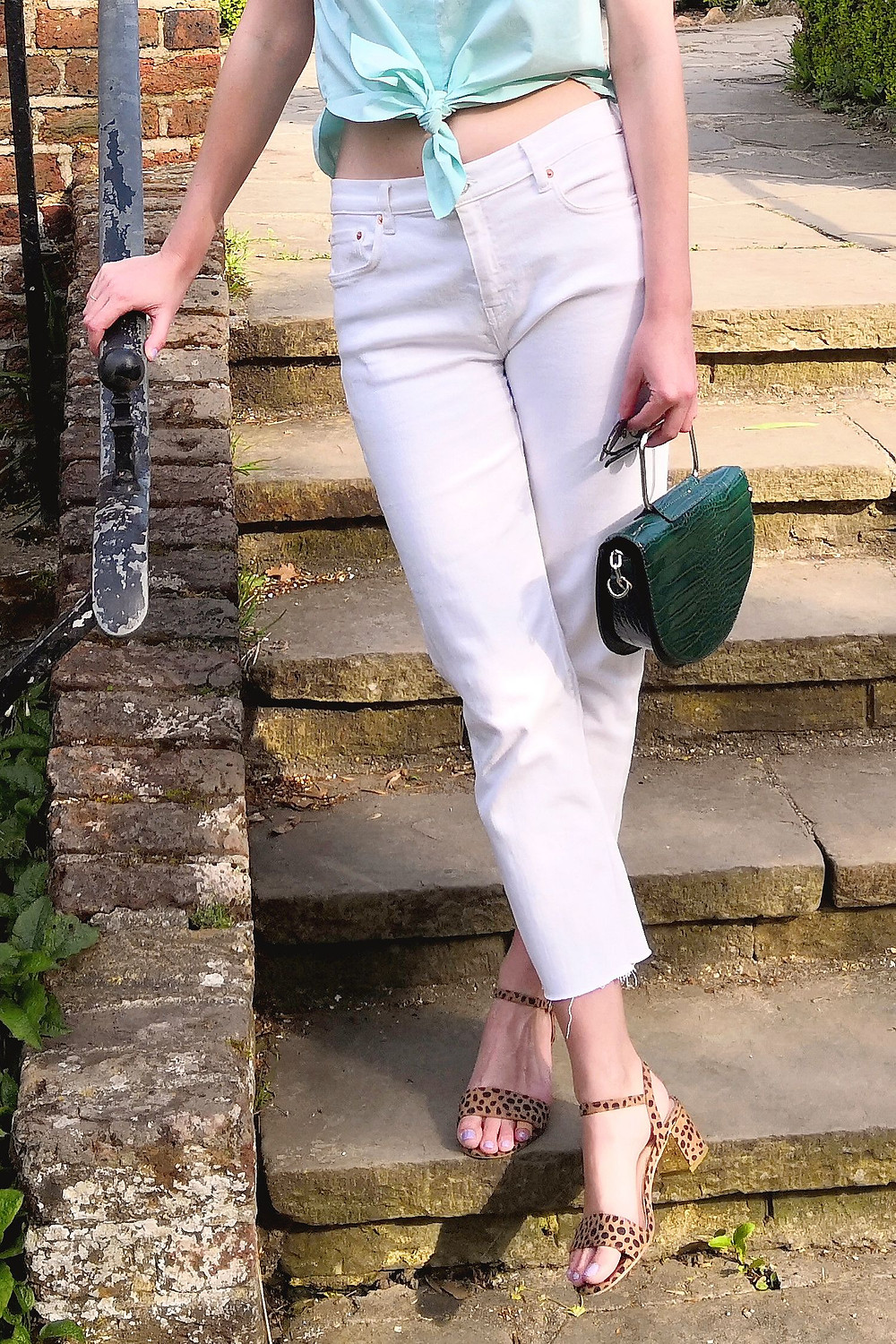 Outfit detail with tie up top, white denim and sandals