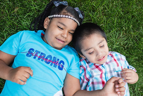 Girl and boy smiling on grass