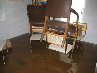 Flood amage in home, chairs stacked wth water below