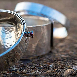close up of silver rivet bangles, photography by Andrew Hyde