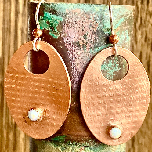 Textured copper oval earrings with an opal