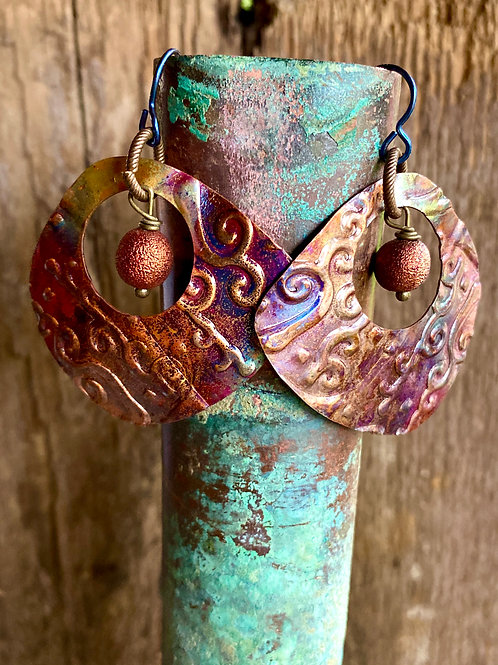 Embossed copper earrings with a multi colored Flame Patina
