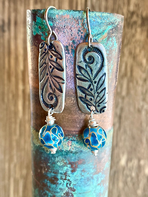 Asymmetrical floral patterned earrings paired with bright blue beads
