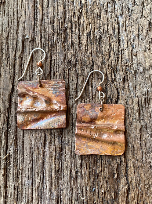 Air chased copper squares with patina
