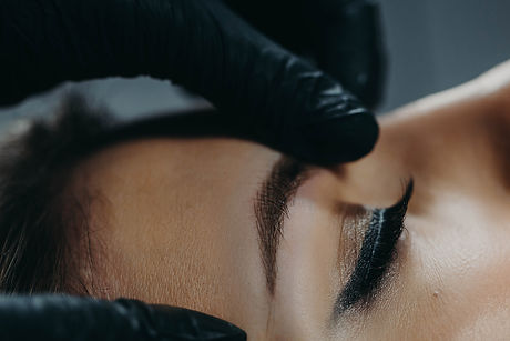 A microblading master in black rubber gl