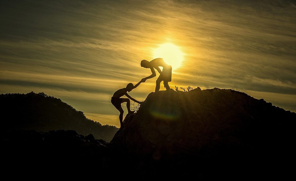 Sunset photograph of two boys climbing a hill silhouetted against the sun and sky with one boy helping the other climb to the top.