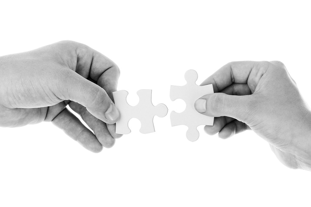 black and white photograph with two hands connecting jigsaw pieces