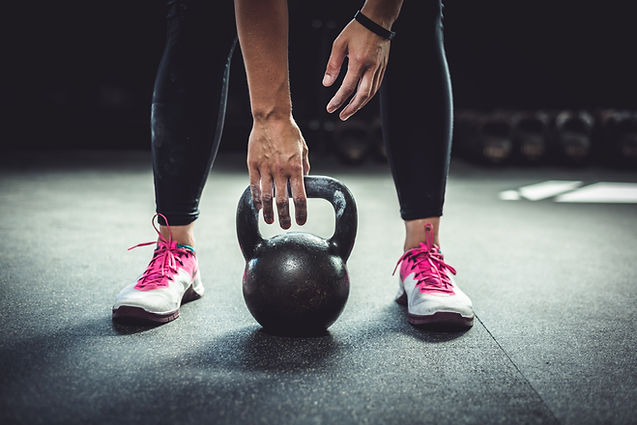 Woman in gym holding a kettlebell. Worki