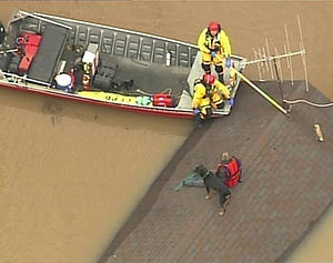 Swiftwater rescue team rescuing man in flood