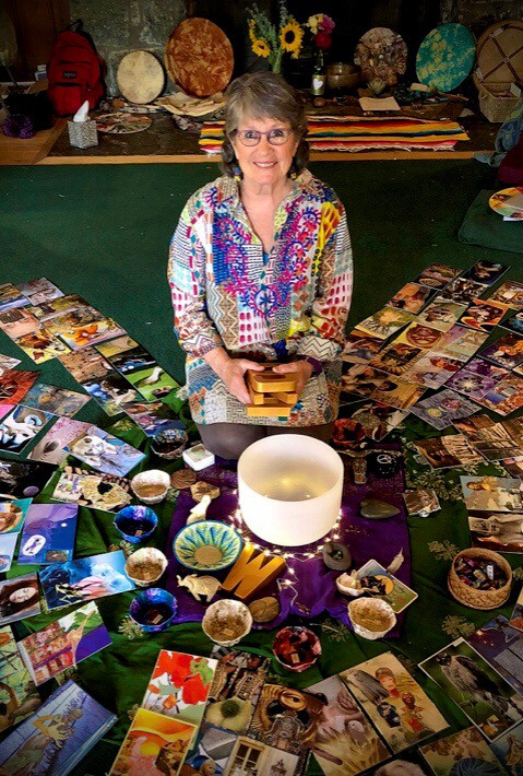 The artists sits in a circle of collaged art cards