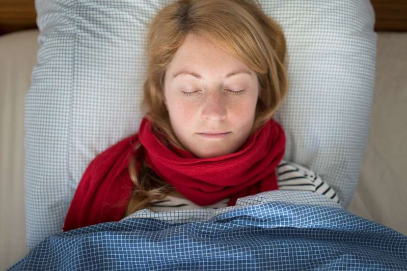 Woman with red scarf, sleeping soundly in her bed