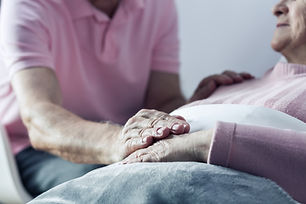 Senior man holding hand of his ill wife,