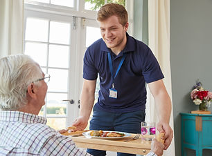 Male care worker serving dinner to a sen