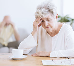 Sad senior woman sitting at a table after a quarrel with her husband.jpg