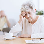 Sad senior woman sitting at a table afte