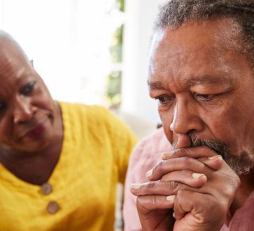 Senior Woman Comforting Man With Depression At Home.jpg