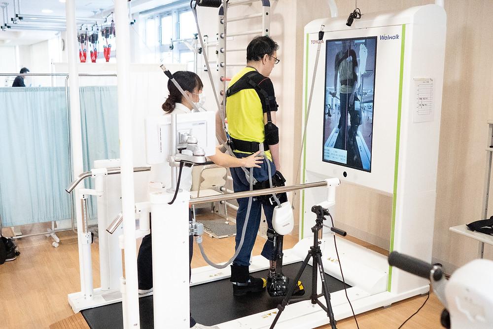 リハビリテーション支援ロボットウェルウォークを用いた歩行訓練を行っている様子です