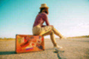 Traveler woman sits on retro suitcase an