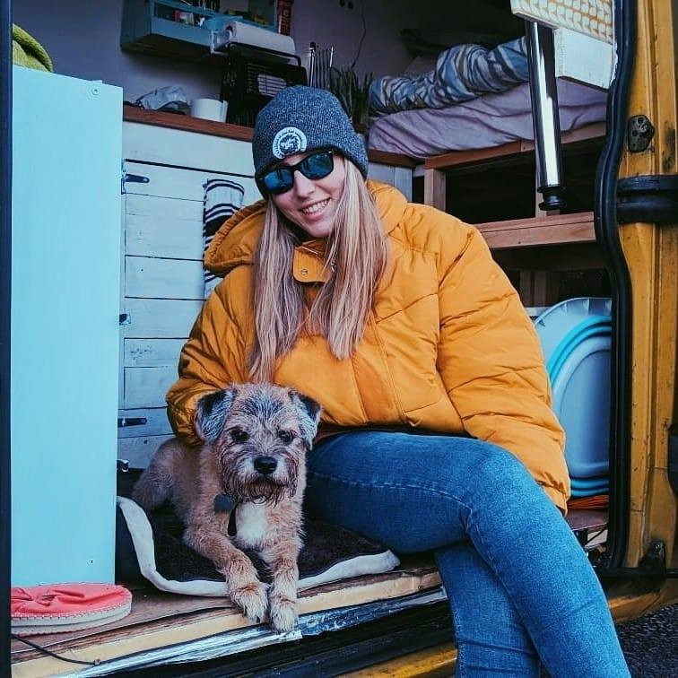 Picture of Emma sat in her campervan with her dog