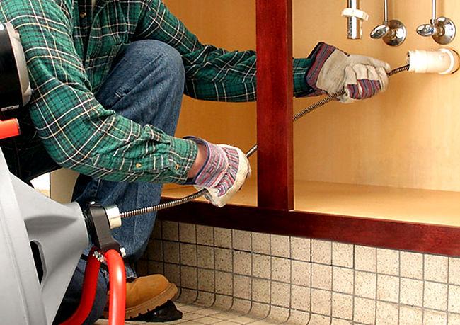 Service tech snaking a bathroom sink