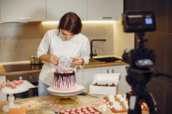 woman-in-white-shirt-decorating-cake-398