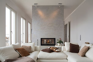 A soffa standing in front of a digital fireplace on a concrete wall