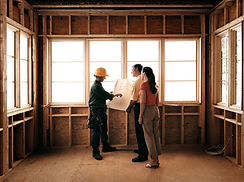 A constructor, a woman and a man looking at architectural plans