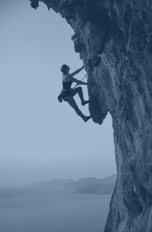 Young woman climbing challenging route a