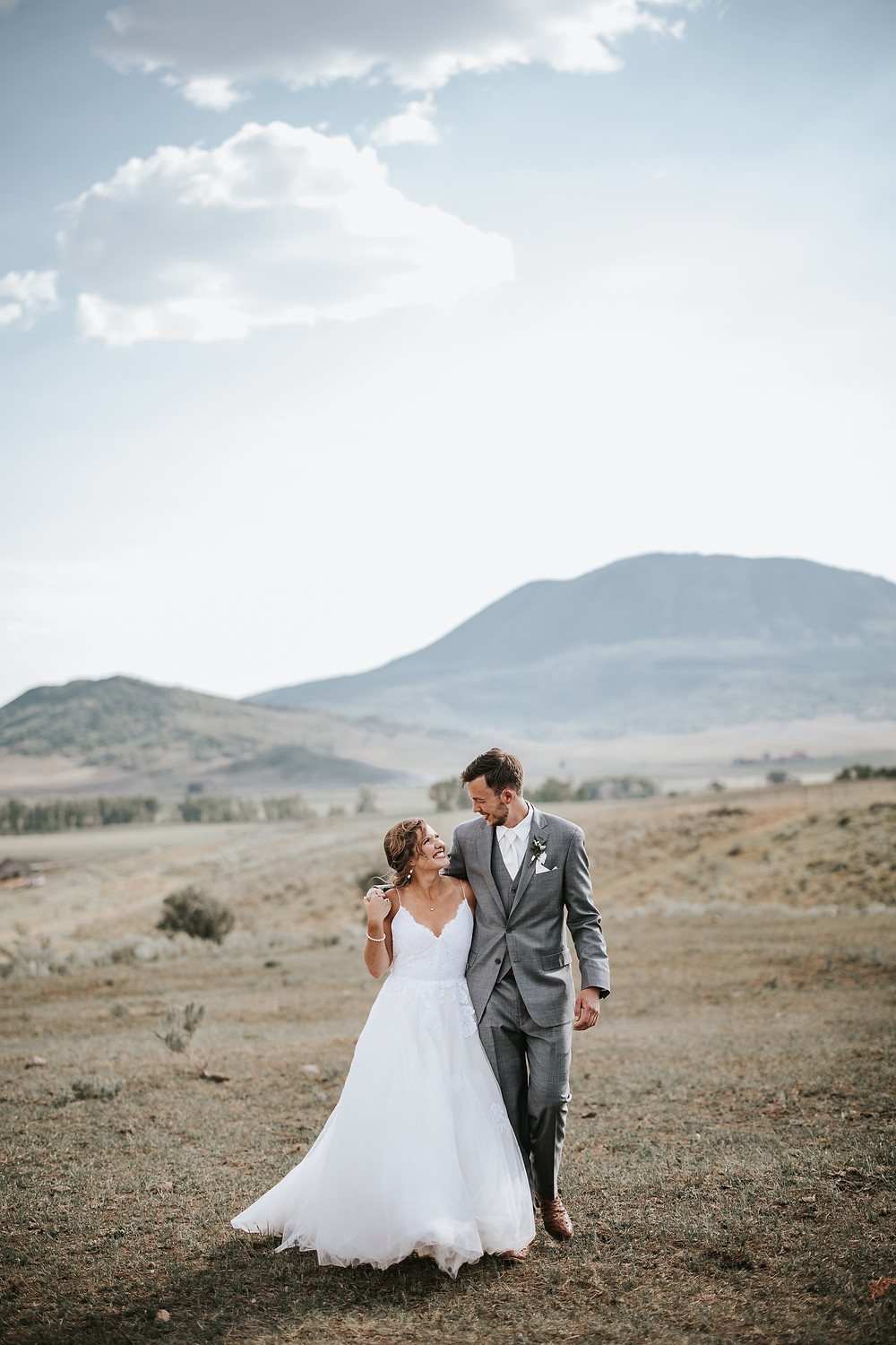 Steamboat Springs elopement couple smiling at each other while walking in the beautiful Rocky Mountain landscape