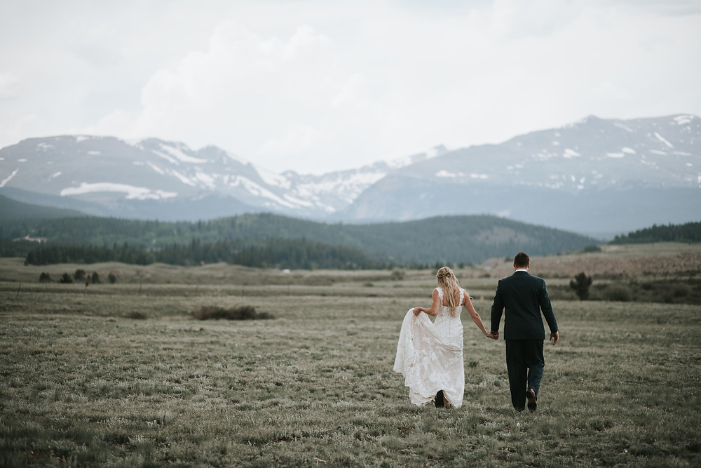 Breckenridge Elopement Couple Holding Hands Walking Into The Mountains