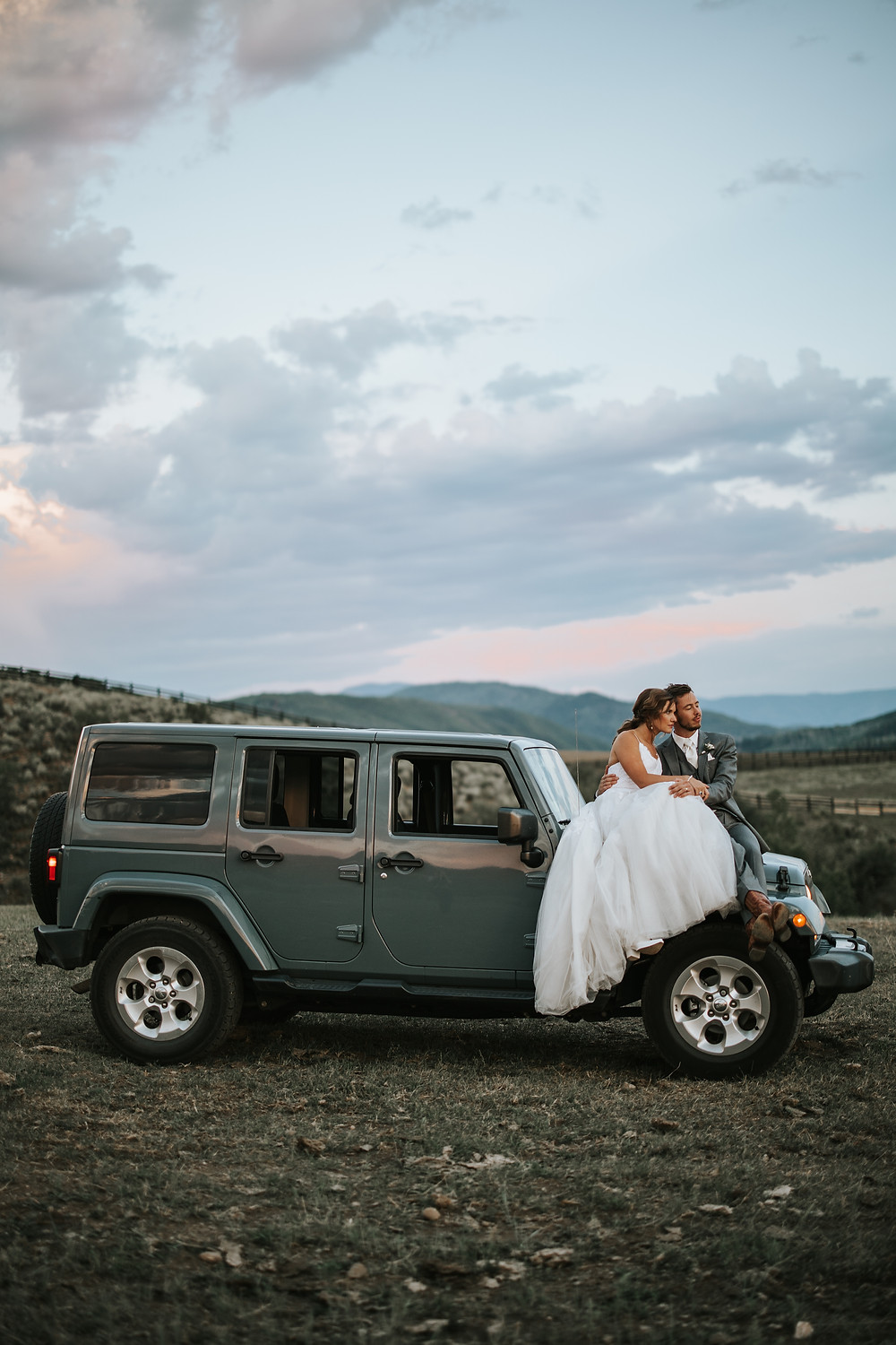 Adventurous elopement couple sitting on their jeep, watching the sunset on their elopement day.