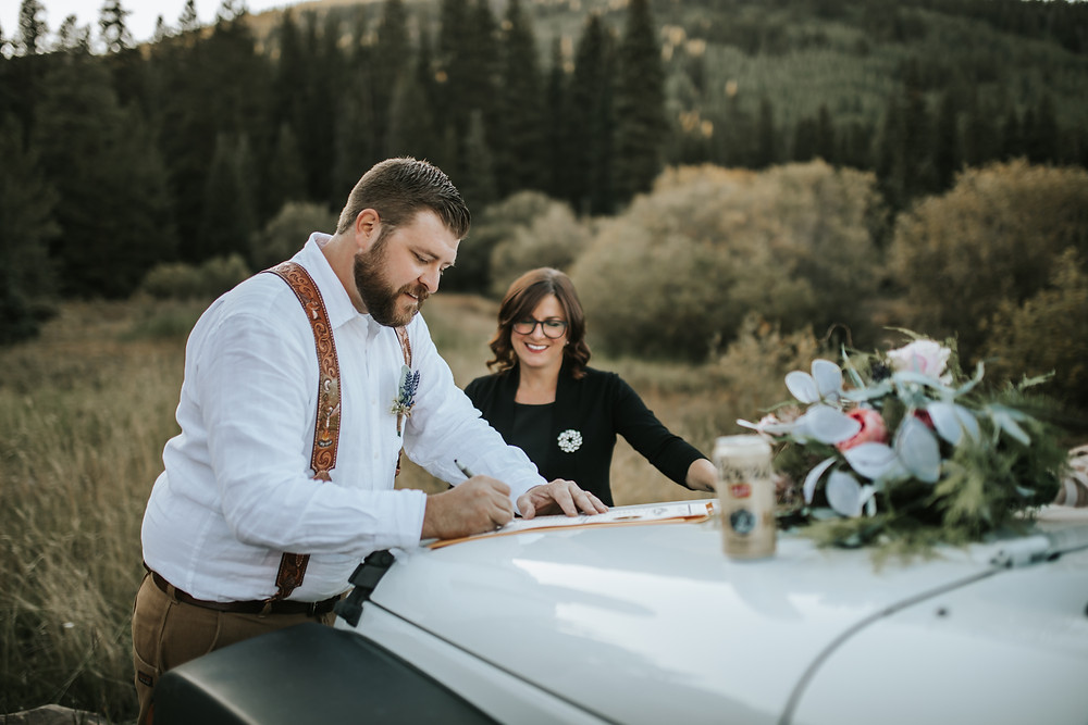Breckenridge eloping couple signing marriage license on their jeep