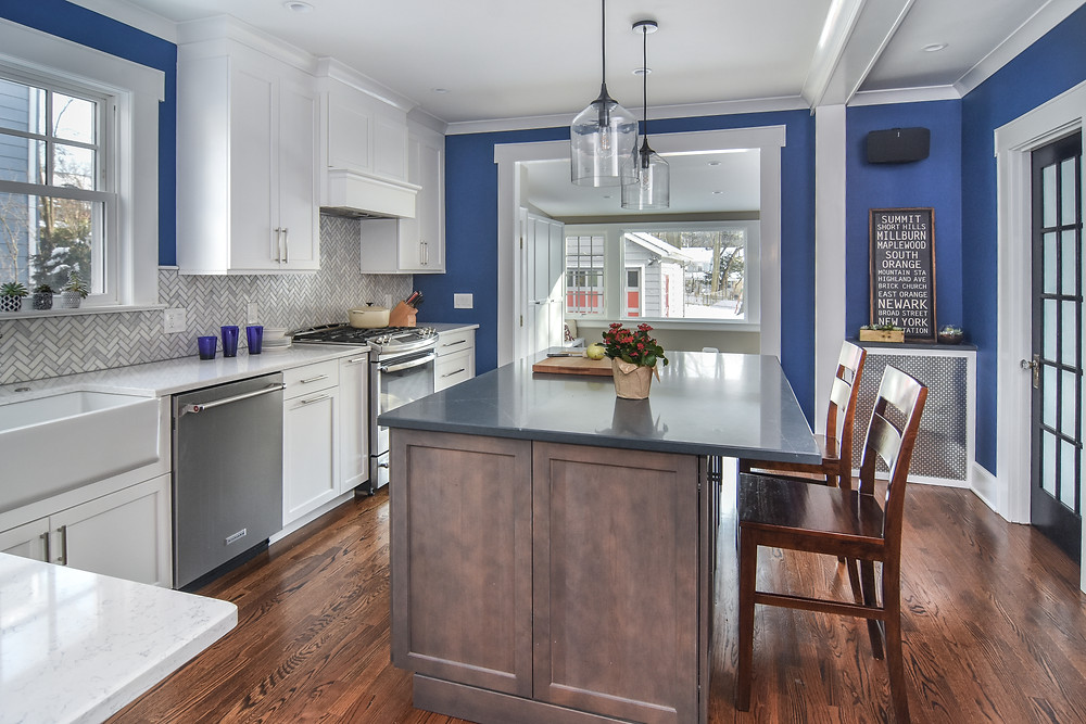 Maplewood, NJ kitchen and family room beyond with blue walls, white and natural wood cabinets, quartz counters, reclaimed French door as pantry door with family room beyond.