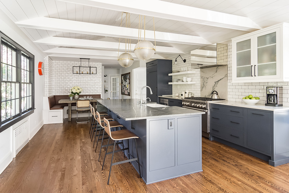 Longitudinal shot of kitchen in Maplewood, NJ. Image shows center island with sink and 4 chairs. Base cabinets are blue-gray. Glass door wall cabinets and shelves are white with subway tile behind Large stove has chrome hood and marble backsplash. Banquet in rear of photo. Exposed rafter ties in vaulted ceiling.